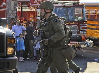 SWAT team member runs to a police car as Sandy Hook Elementary School is evacuated after a shooting