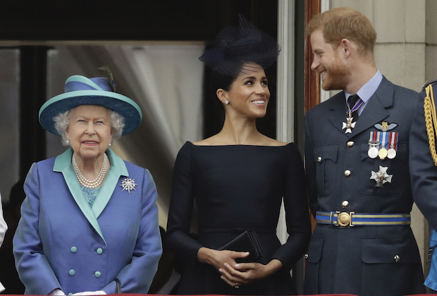 FILE - In this Tuesday, July 10, 2018 file photo Britain's Queen Elizabeth II, and Meghan the Duchess of Sussex and Prince Harry watch a flypast of Royal Air Force aircraft pass over Buckingham Palace in London. Prince Harry and his wife Meghan are ending their lives as senior members of Britain's royal family and starting an uncertain new chapter as international celebrities and charity patrons. In January the couple shocked Britain by announcing that they would step down from official duties, give up public funding, seek financial independence and swap the U.K. for North America. The split becomes official on March 31. (AP Photo/Matt Dunham, File)