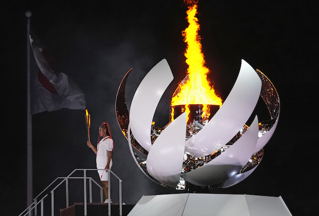 Naomi Osaka stands beside the Olympic flame during the opening ceremony in the Olympic Stadium at the 2020 Summer Olympics, Friday, July 23, 2021, in Tokyo, Japan. (AP Photo/Petr David Josek)